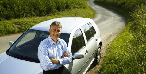άντρας κάθετε στο καπό του αμαξιού του και χαμογελάει έχοντας σταυρωμένα τα χεριά του στην εξοχή